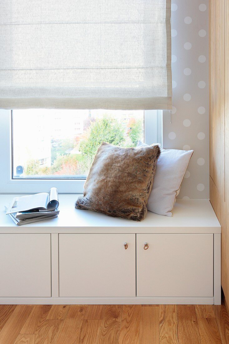 Cushions on low, white sideboard below window with Roman blind