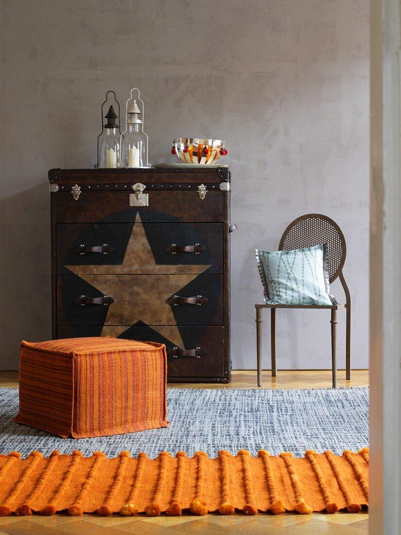 Orangefarbener Sitzwürfel und Läufer, an Wand Kommode und Stuhl im Ethnostil