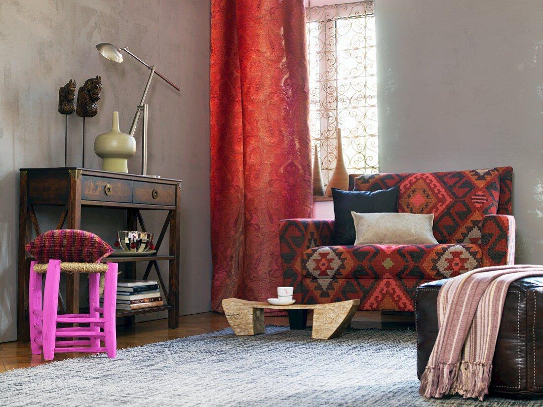 Wohnbereich in afrikanischem Stil - Sideboard, roter Vorhang, Sofa mit gemustertem Bezug und Lederpouf