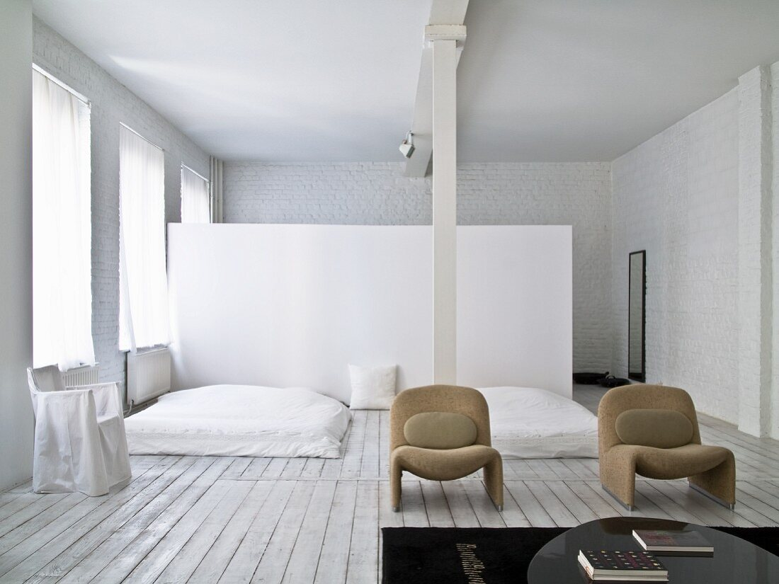 Sleeping area with wooden floor, white-painted brick walls and partition in background