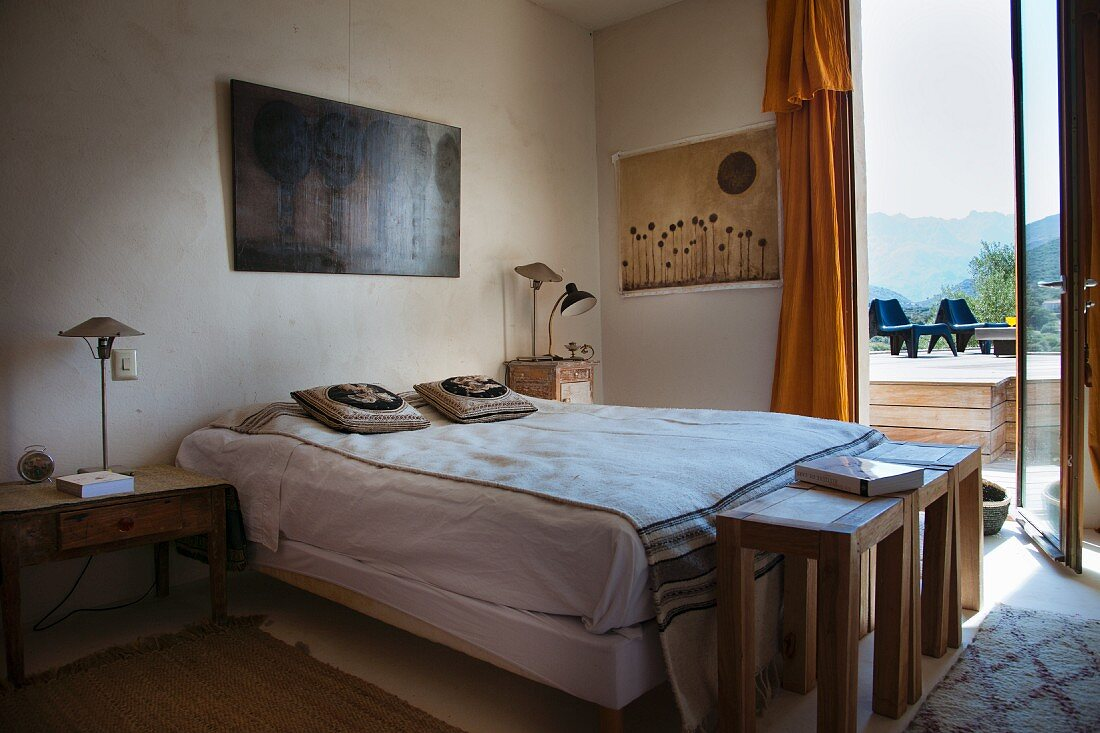 Ethnic-style bedroom with three wooden stools at foot of bed and view through open French windows