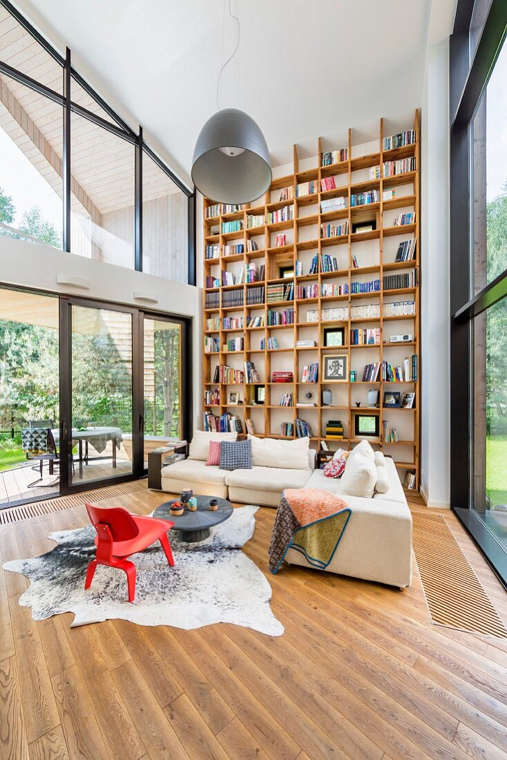 Red classic armchair on animal-skin rug and pale corner sofa in contemporary building with floor-to-ceiling bookcases on one wall