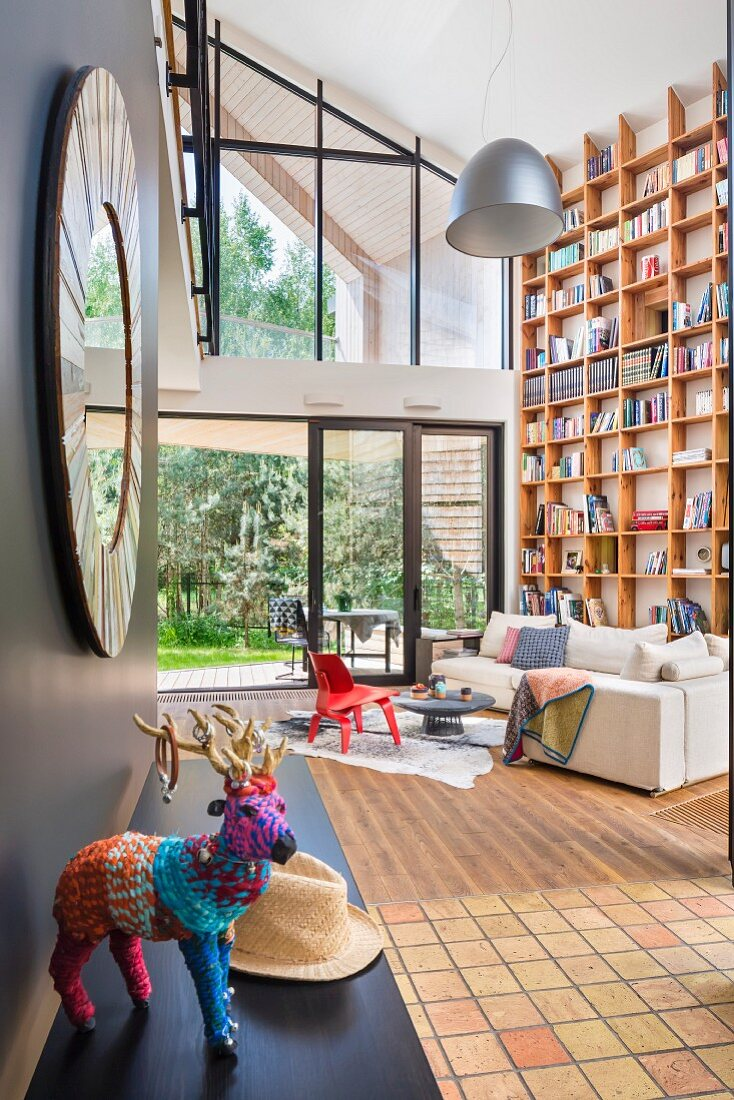 Animal ornament covered in colourful yarn on black shelf and sofa in front of floor-to-ceiling bookcase in contemporary living room