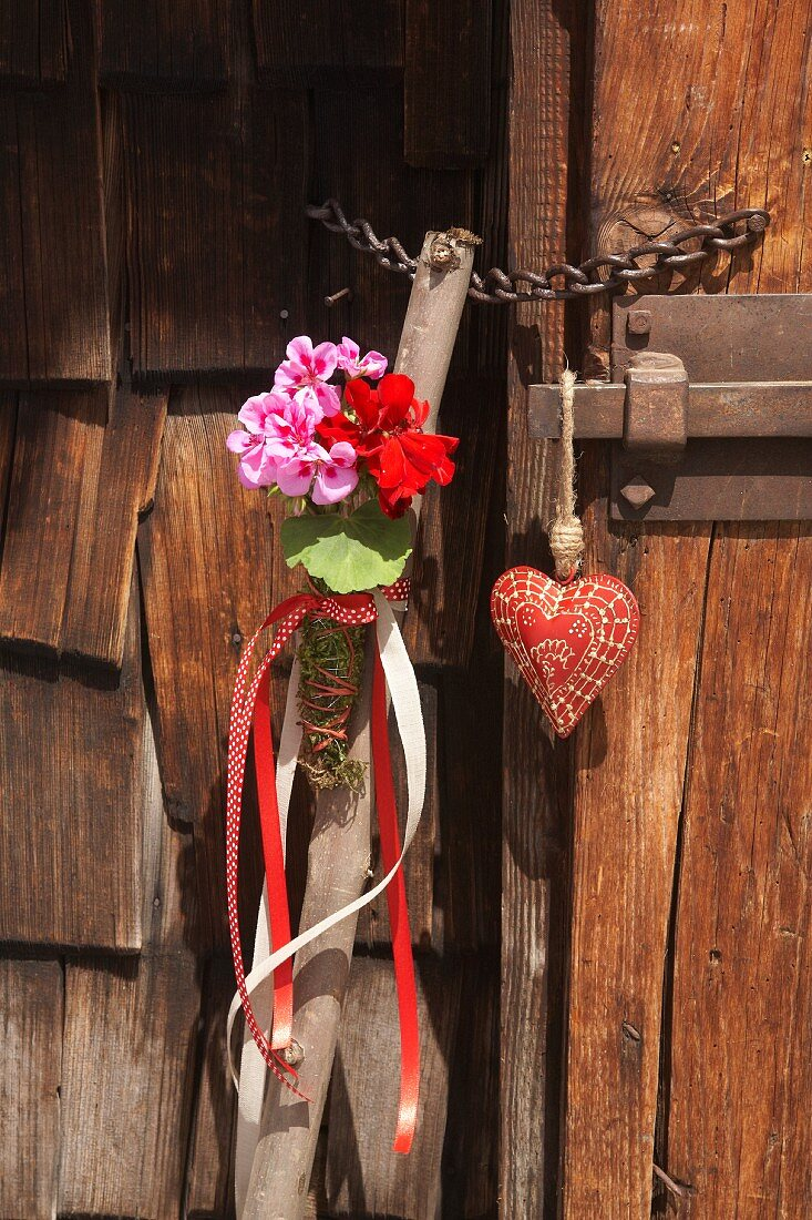 Walking stick decorated with geraniums next to small fabric heart hung on wooden door