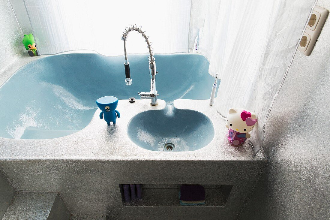 Small, colourful figurines on organically shaped, pale blue sinks recessed in monolithic washstand with silver-painted surface