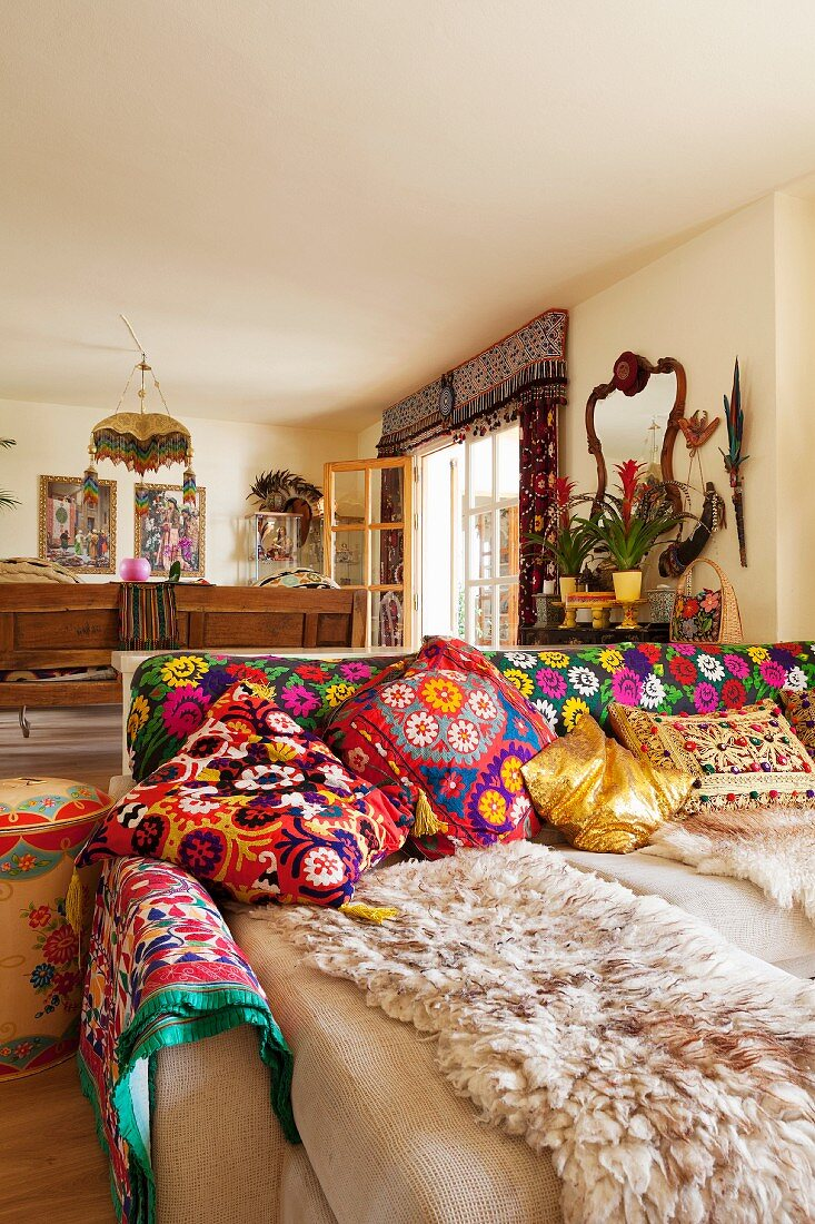 Sofa with various brightly patterned scatter cushions and blankets in comfortable, ethnic-style living room