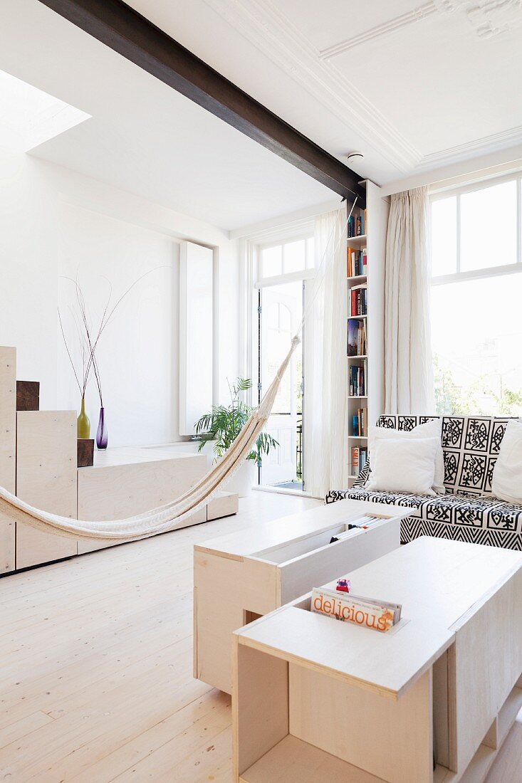 Hammock casually hung between custom furniture made from pale wood in bright interior