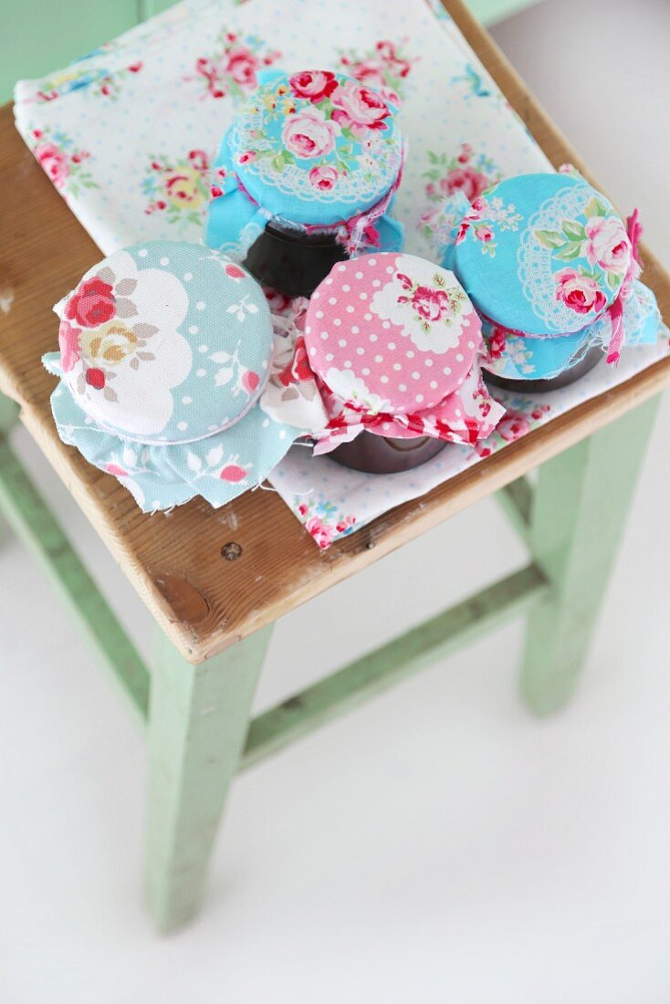Jam jars with pastel, rose-patterned fabric lids on vintage stool
