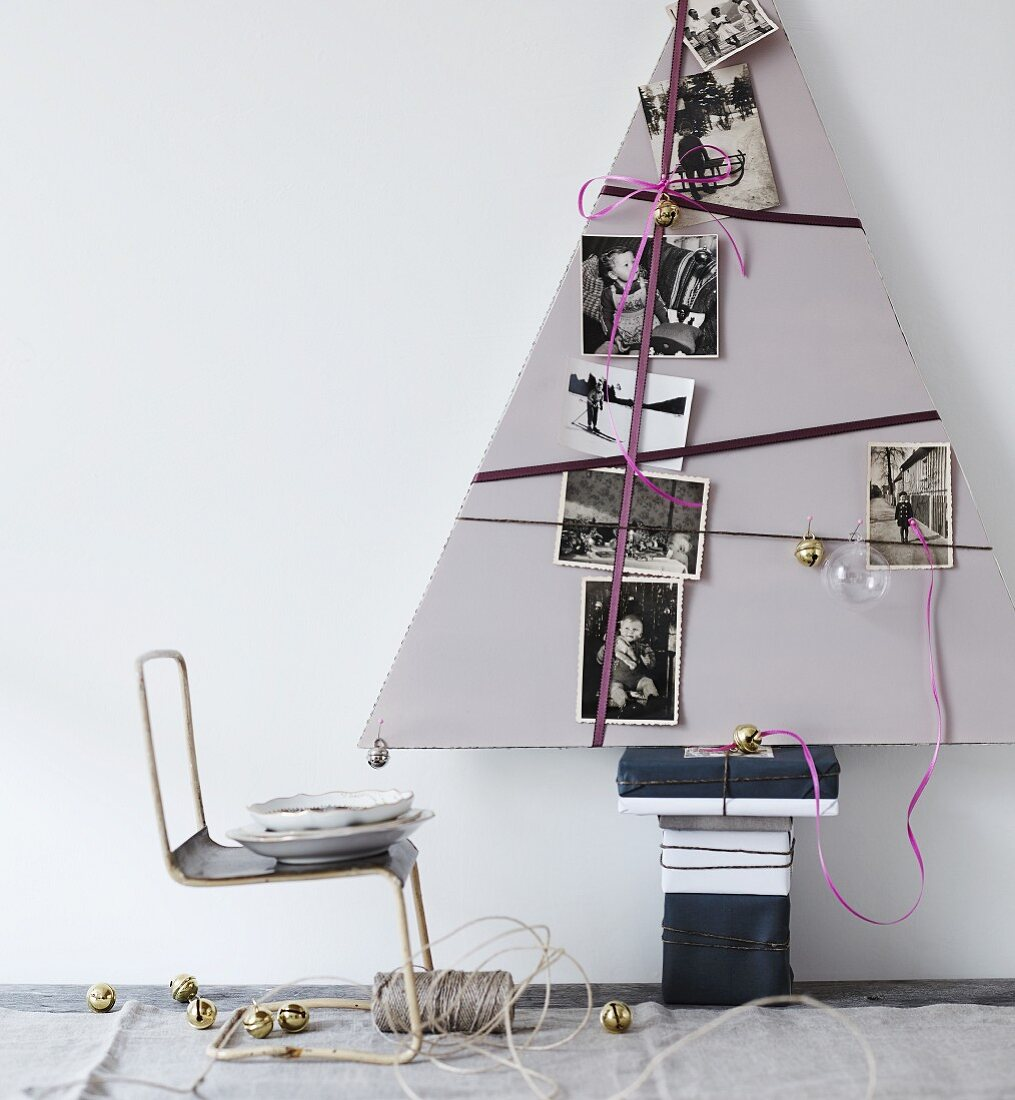 Stylised, triangular, cardboard Christmas tree decorated with ribbons and black and white family photos