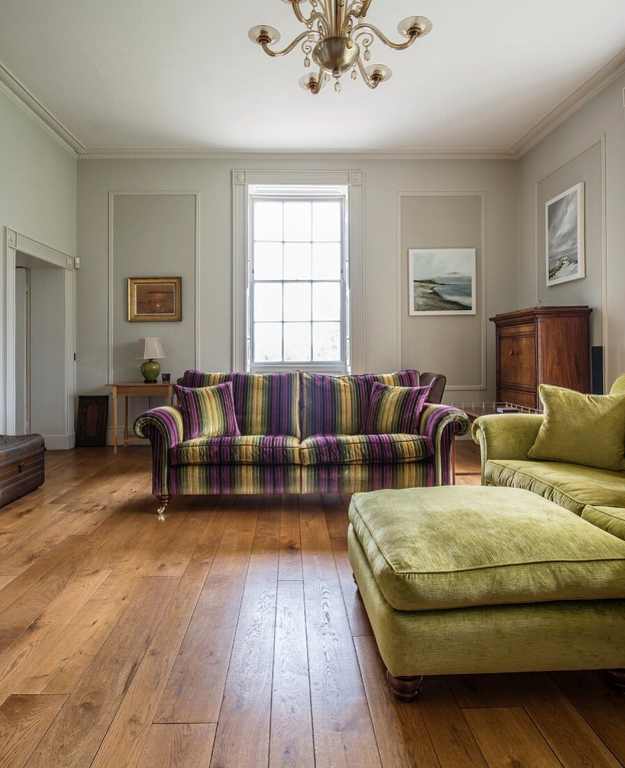 Green ottoman and couch and striped couch in spacious living room