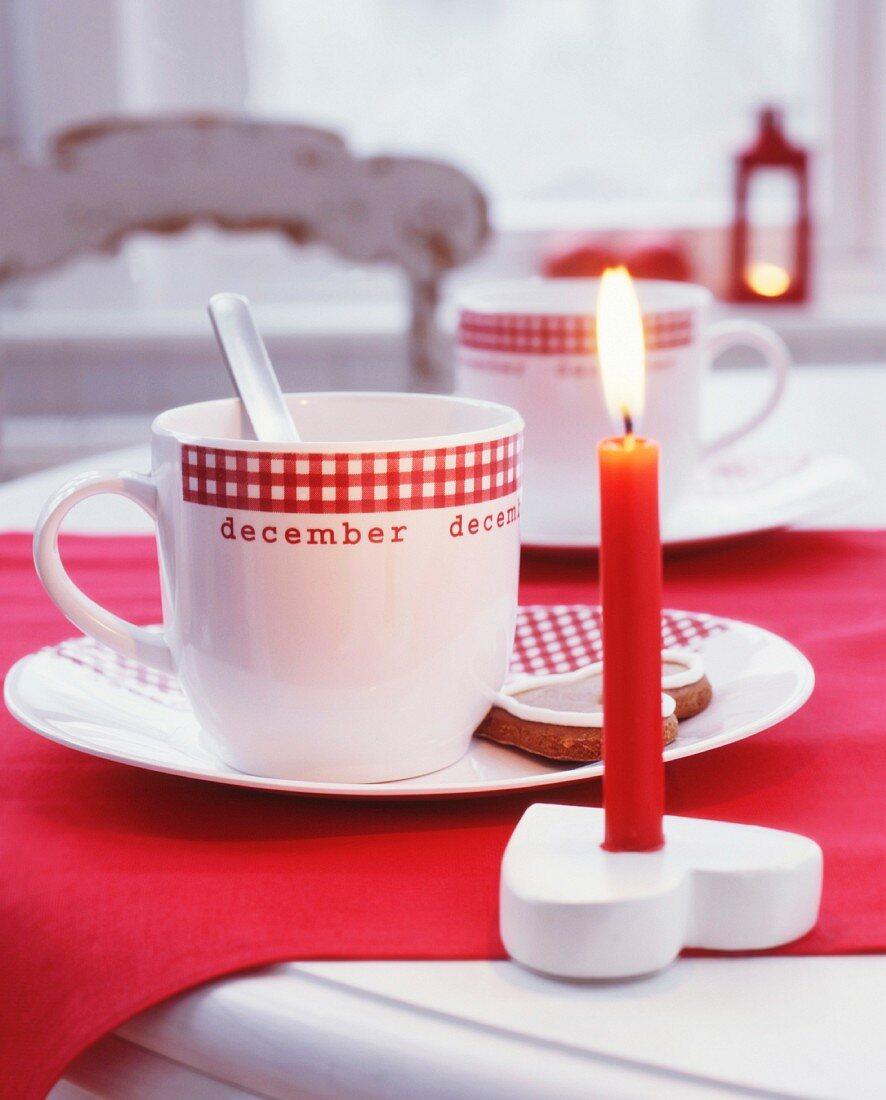Rote, brennende Kerze im herzförmigen Kerzenhalter und Tassen mit Karo-Dekor