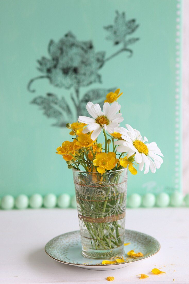Wildflowers in glass in front of green canvas printed with floral pattern