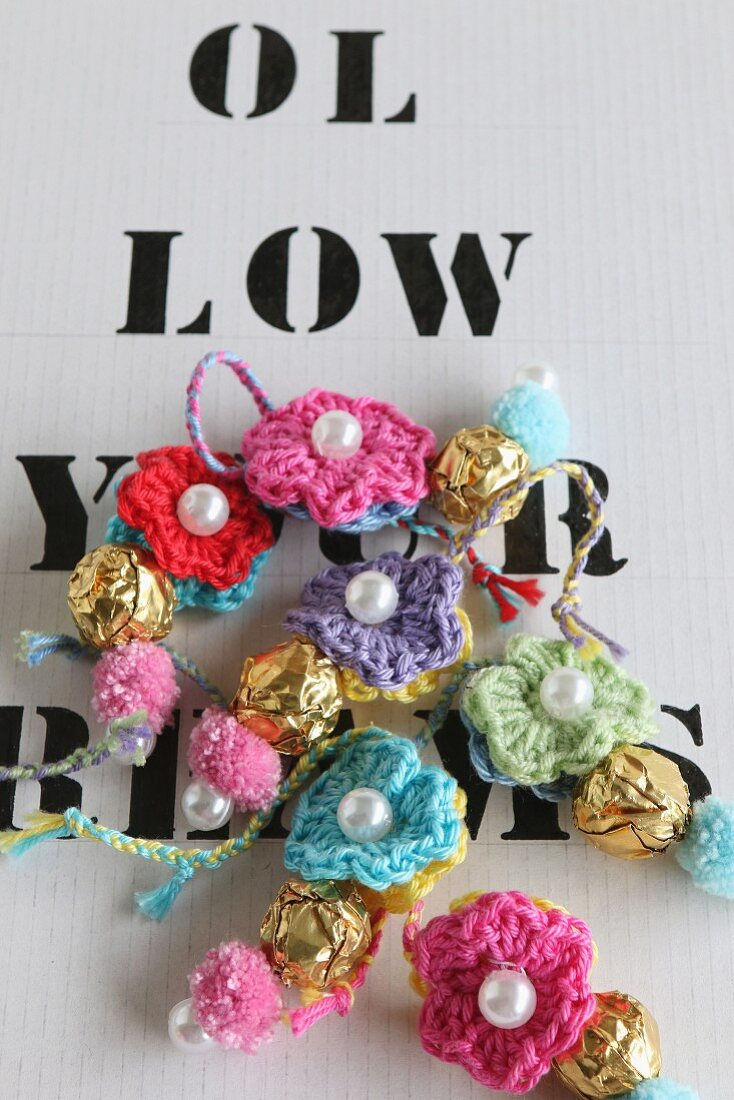 Colourful woollen pendants with sewn-on beads on paper with hand-printed letters