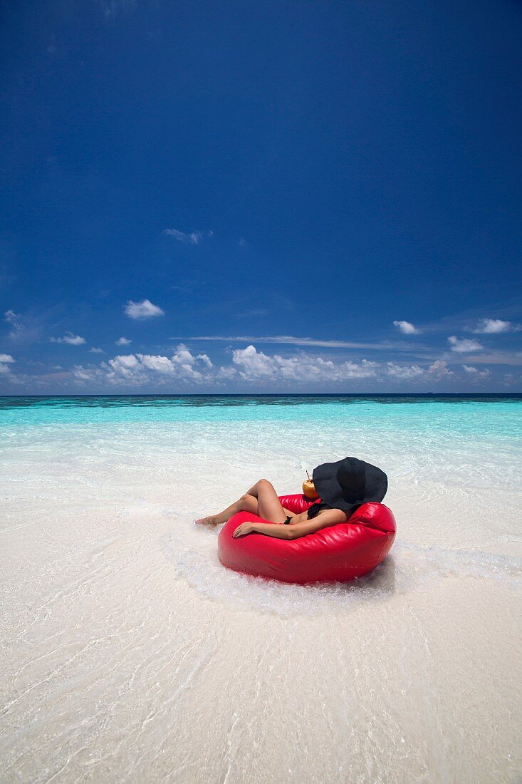 Woman relaxing on beanbag on Maldives beach