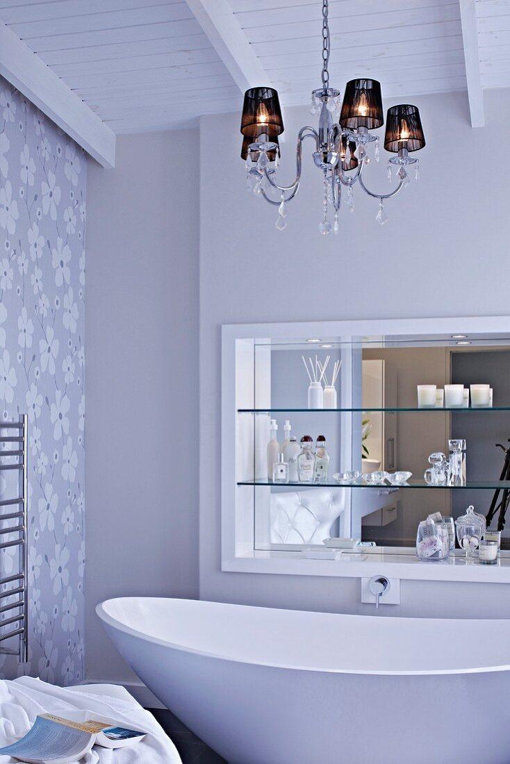 Chandelier above free-standing, designer bathtub; shelves in niche with mirrored wall