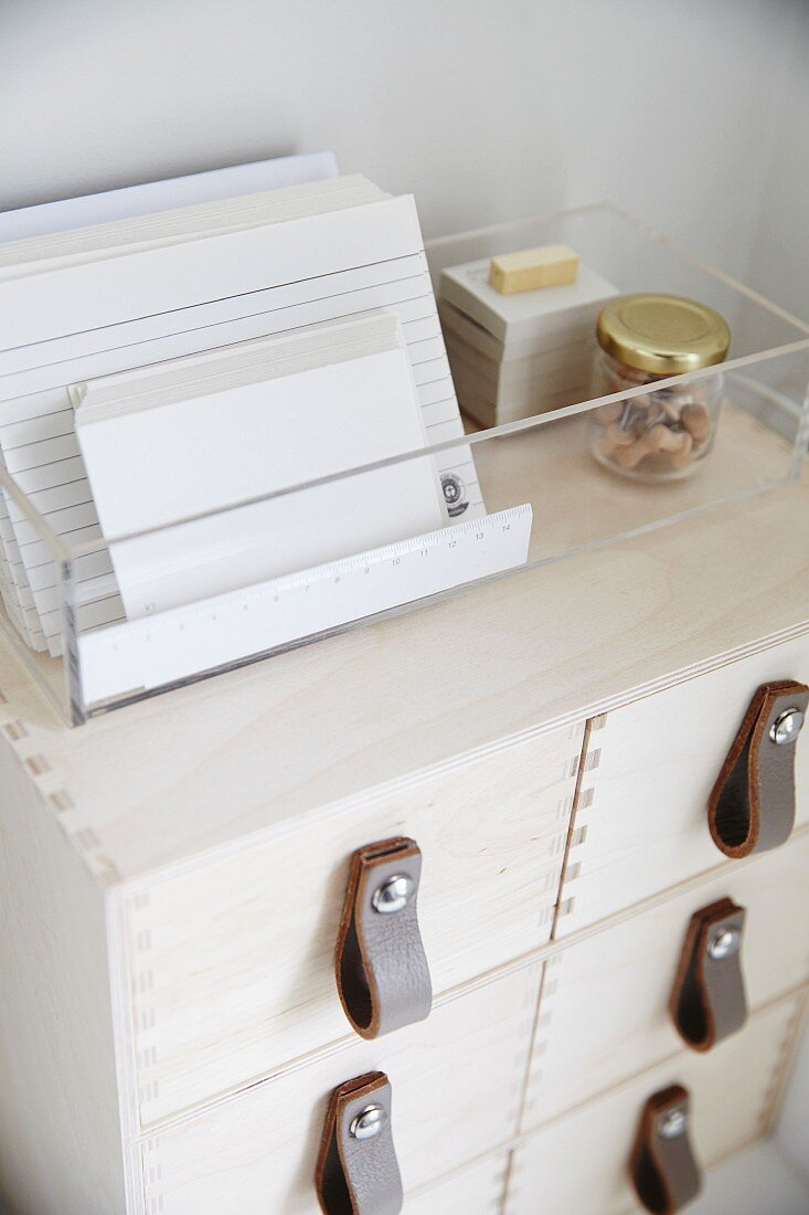 Index cards in transparent plastic box on top of wooden filing cabinet with leather handles
