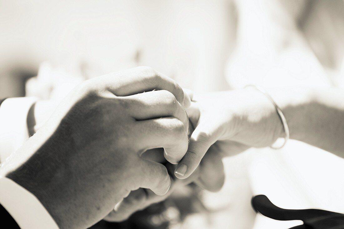 Man putting wedding ring on wife's finger