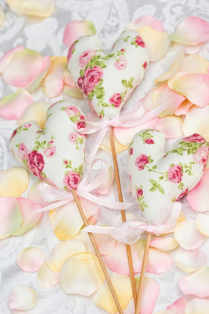 Floral, fabric love-hearts on wooden sticks as wedding decorations