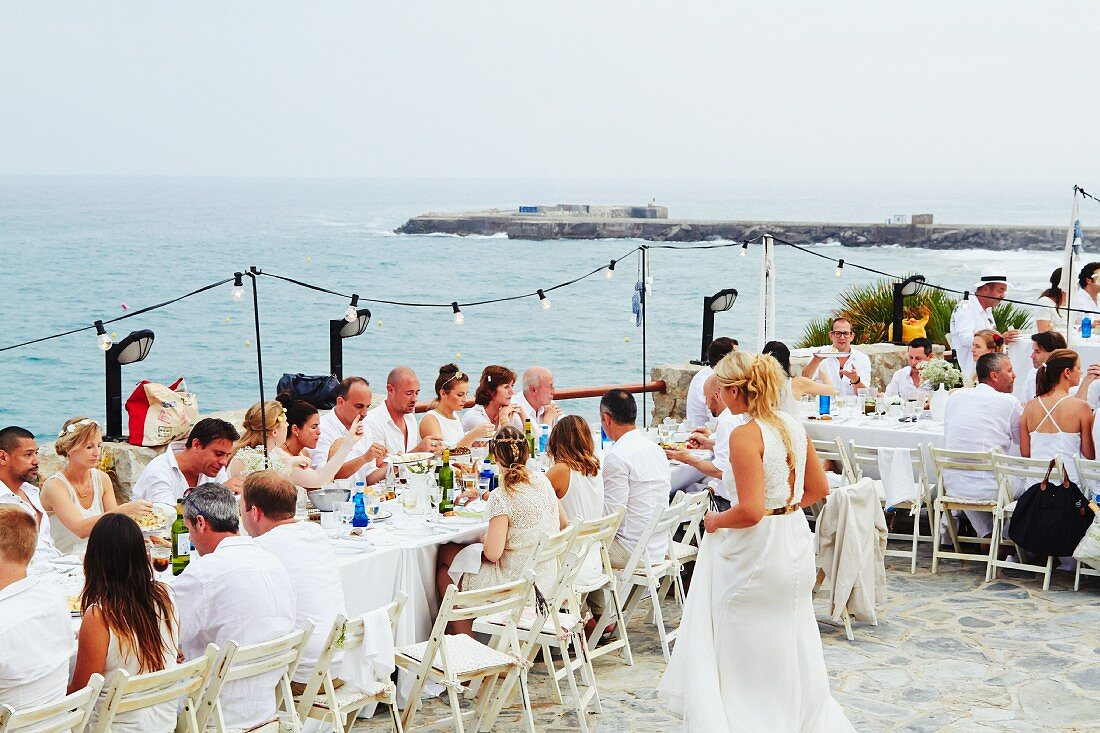 Wedding guests seated at long dining table by the sea