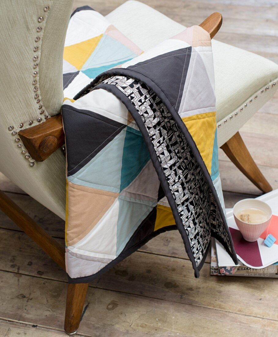 A quilted blanket on the arm of an upholstered chair