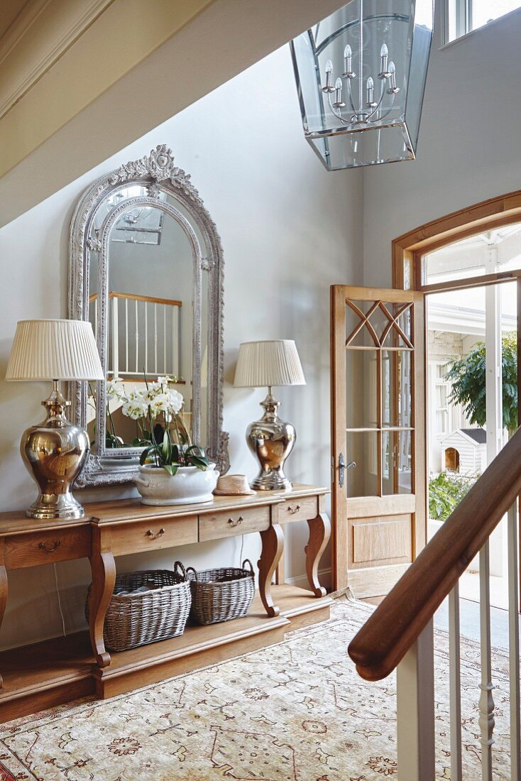 Hallway in French country-house style with ornately framed mirror above console table and pair of lamps
