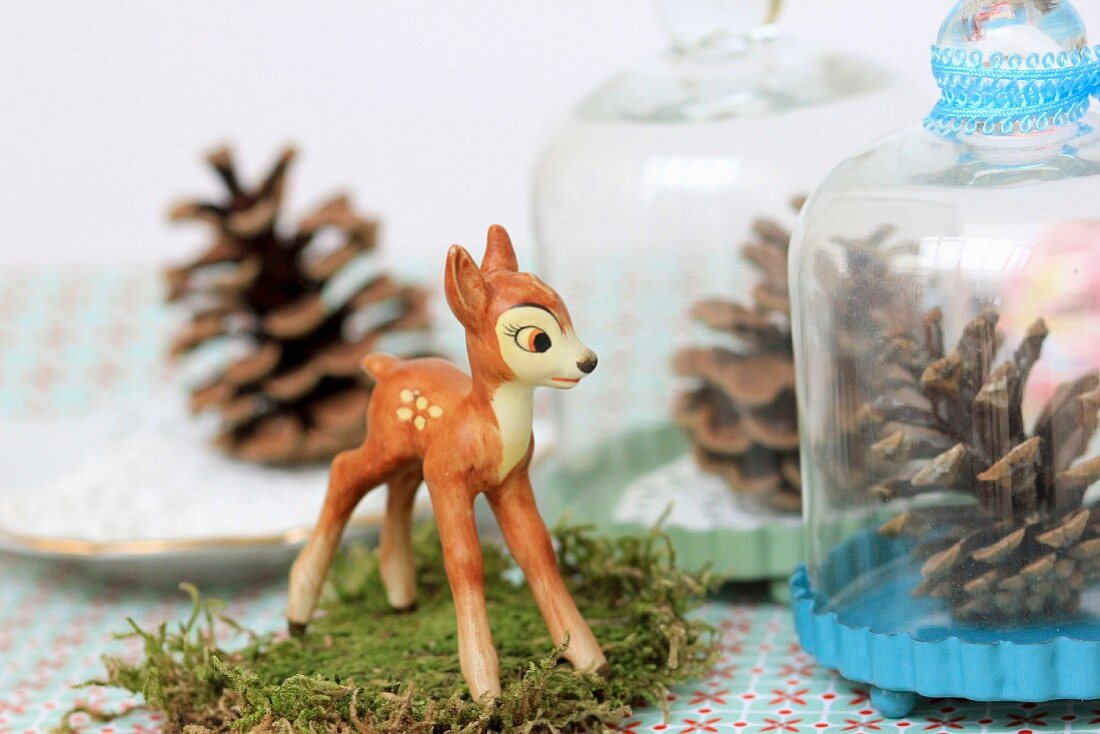 Winter arrangement of fawn figurine on moss & pine cone under glass cover