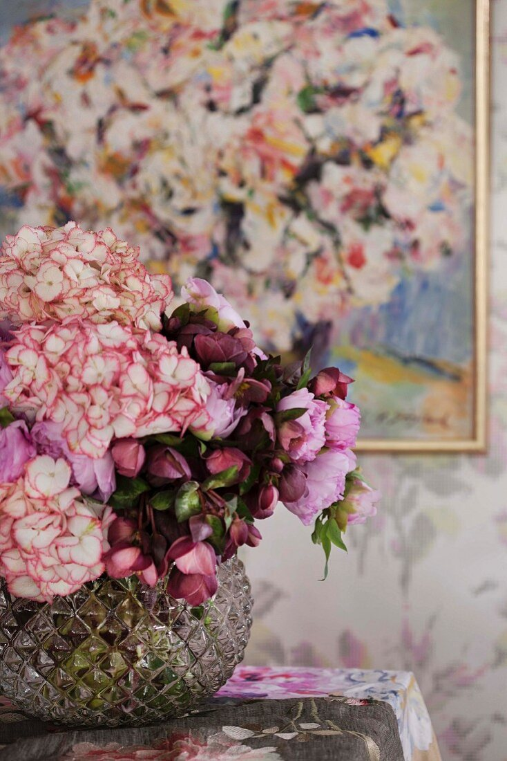 Romantic bouquet in glass vase on table in front of painting on wall