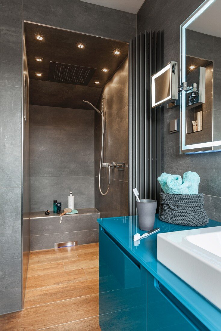 A petrol-coloured washstand with a grey-tiled shower in the background with built-in spot light in the ceiling
