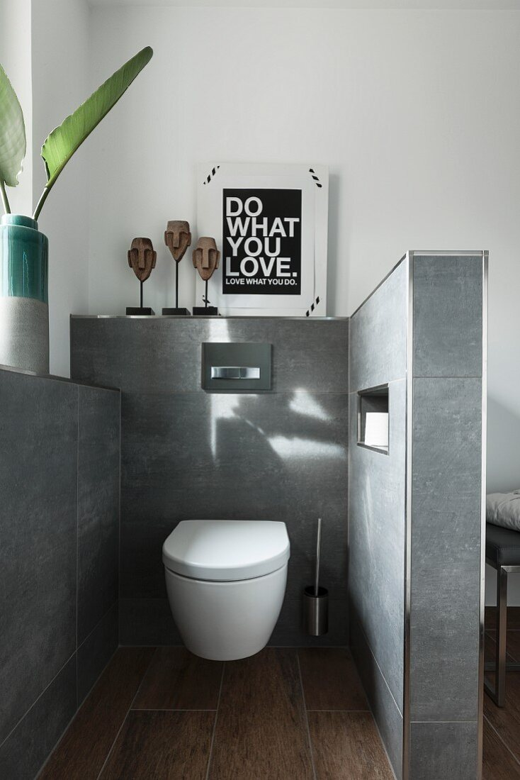 A separate toilet corner with a wall-mounted toilet on a grey-tiled wall