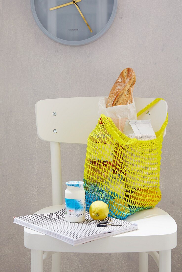 A homemade, yellow crocheted shopping bag on a white kitchen chair