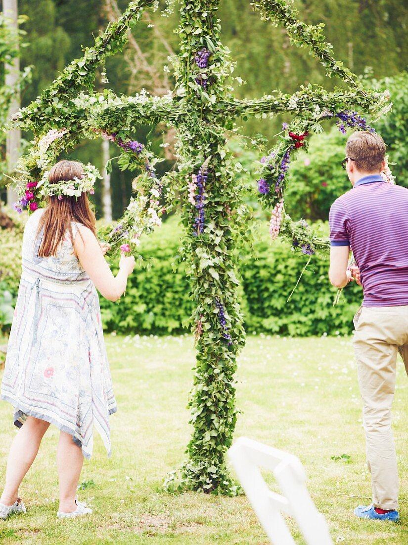 Young couple decorating garden for midsummer festival