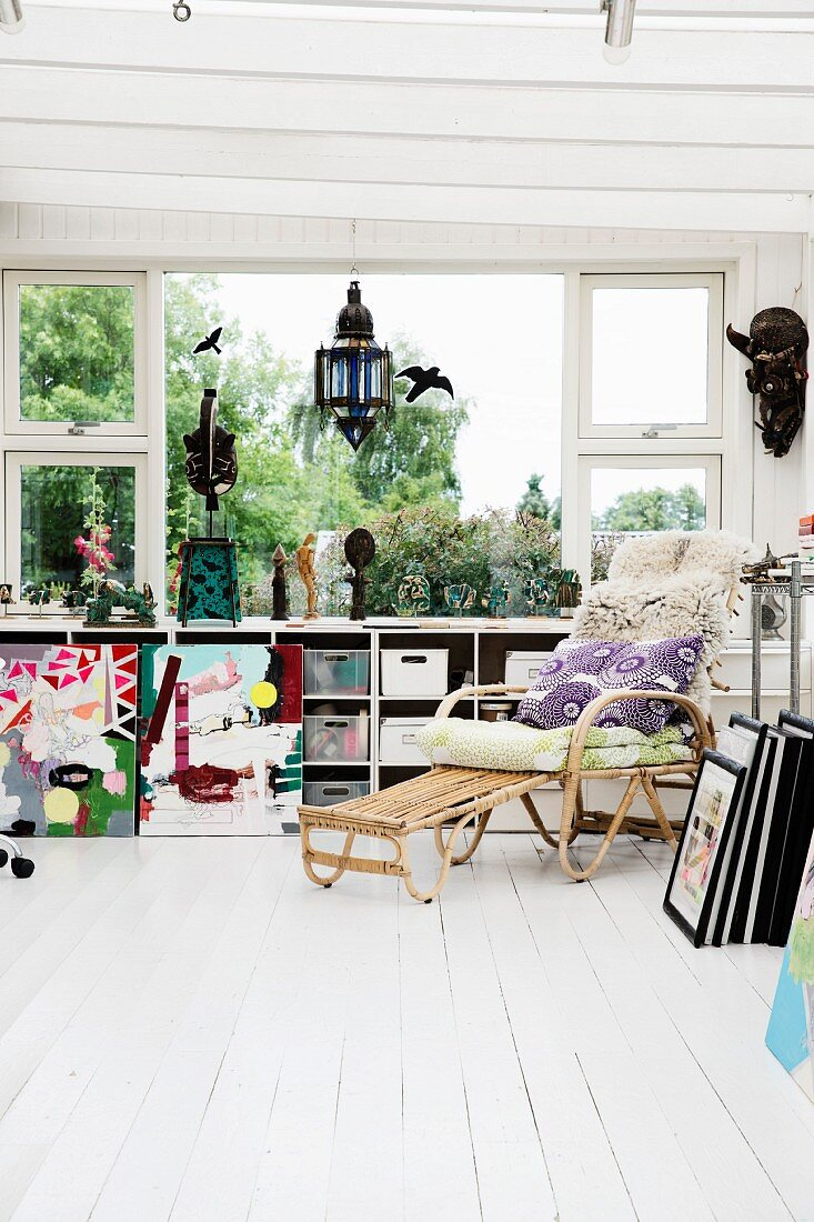 Cushions and fur rug on comfortable wicker lounger on white wooden floor in front of window with storage boxes on fitted shelving below sill