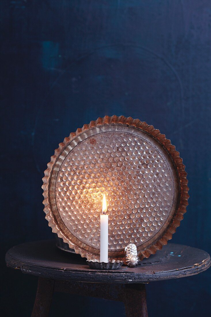 An old baking tin in candlelight as a Christmas decoration