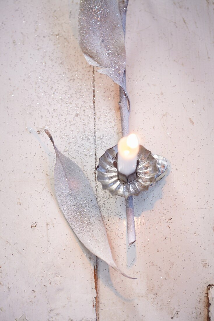 A Christmas tree candle, eucalyptus leaves and silver glitter as decorative material