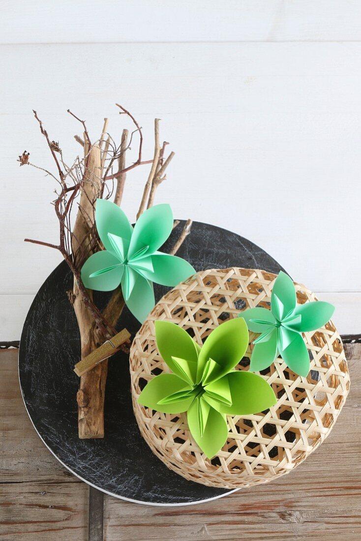 Grüne Origami-Blüten auf einem Ast und Bastkörbchen