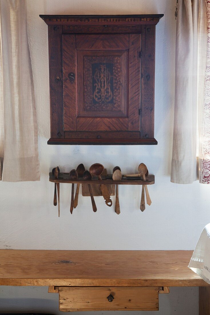 Old wall-mounted cabinet above wooden spoons in rack