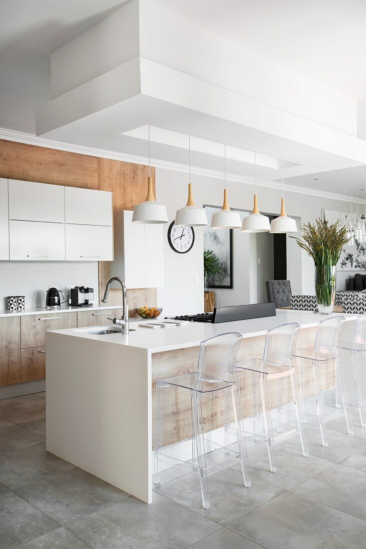 Transparent bar stools at island counter in modern kitchen