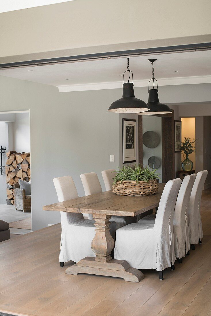 Chunky wooden table and loose-covered chairs in dining area