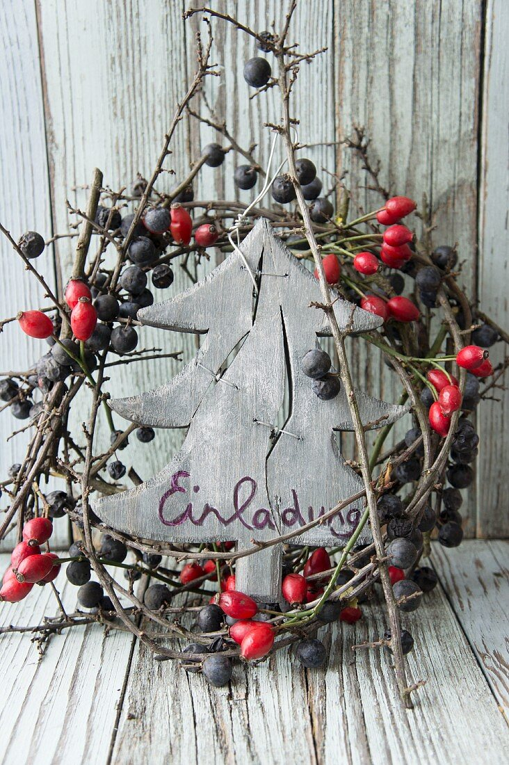 Invitation on wooden tree in wreath of berries