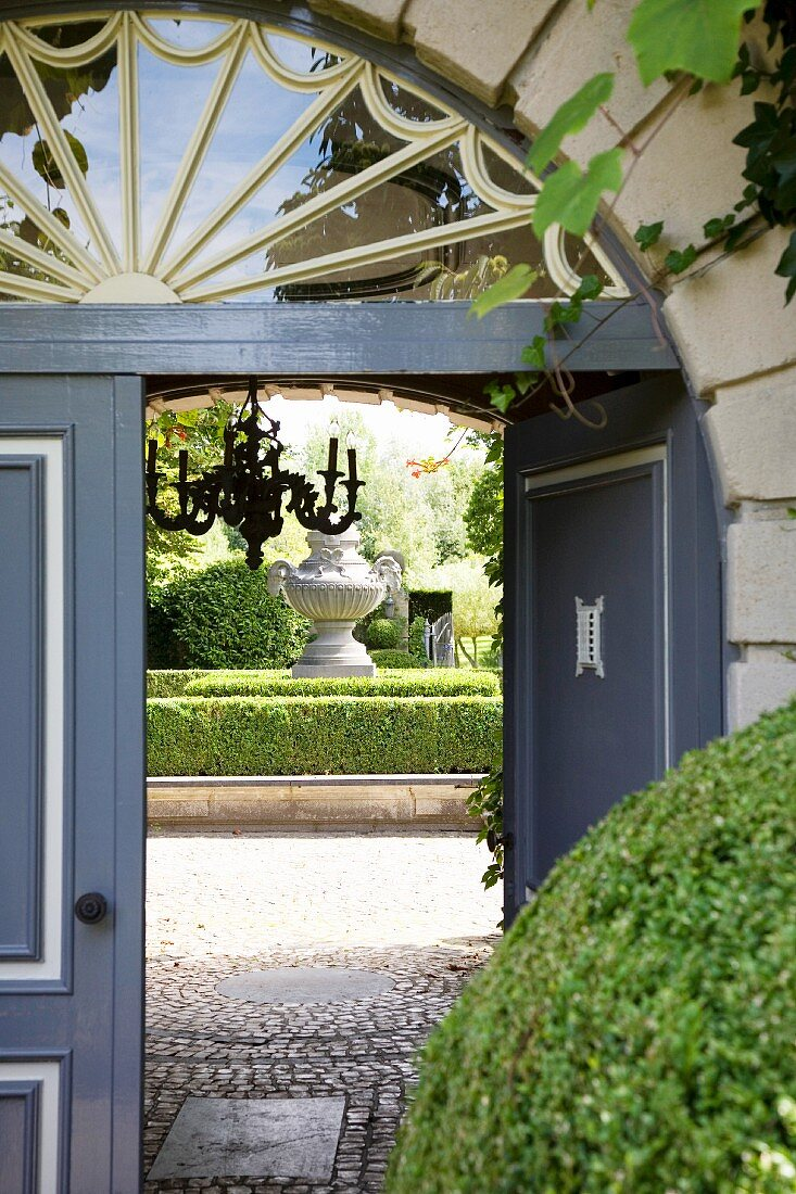 View through arched doorway into elegant courtyard with gardens