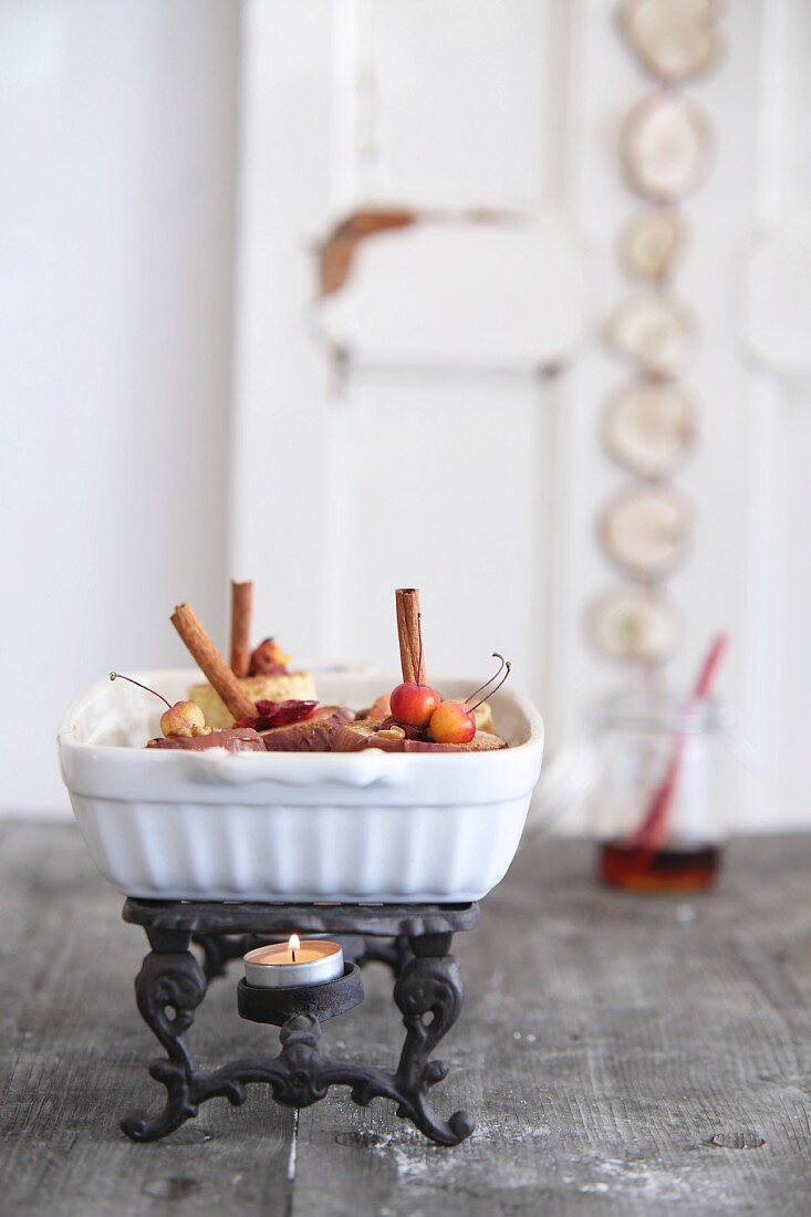 Baked apples with cinnamon sticks and crab apples in casserole dish on vintage warmer