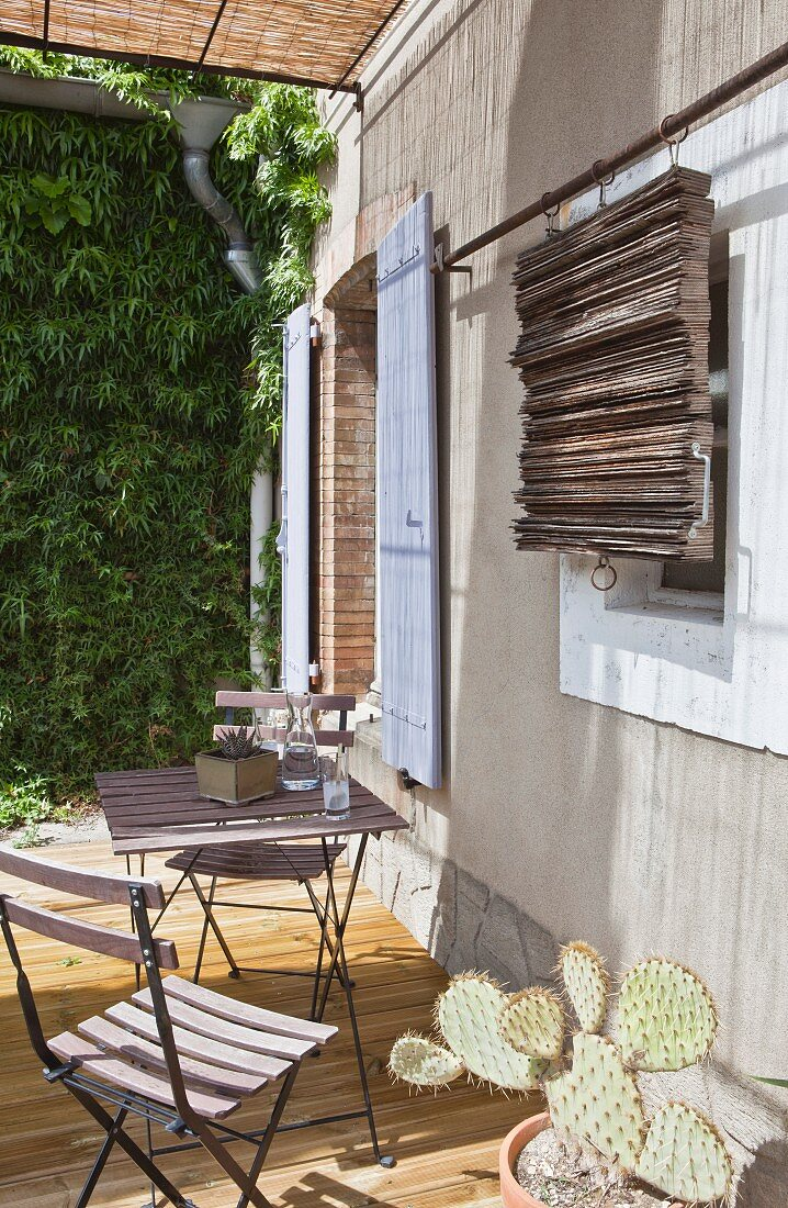 Folding furniture on wooden terrace and sliding wooden shade shutters
