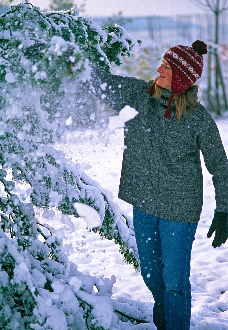 Junge Frau schüttelt Schnee von den Zweigen
