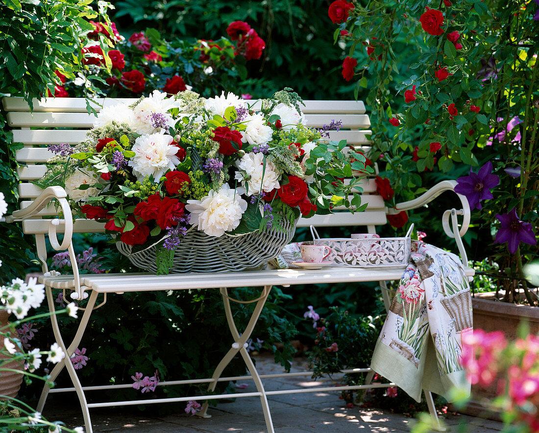 Garden bench with climbing rose 'Flammentanz', basket with arrangement