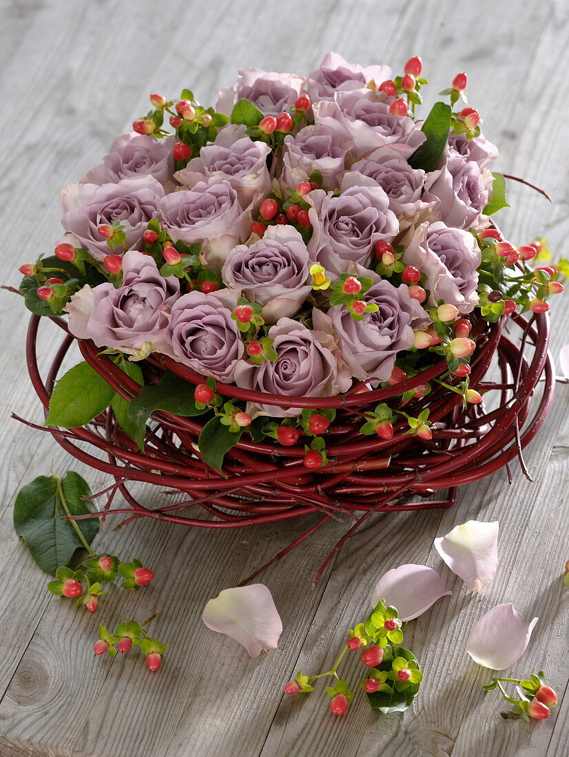 Arrangement of purple roses and St. John's wort fruits in wreath of dogwood branches