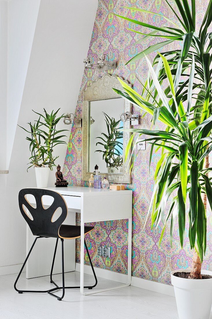 Dracaena and dressing table against patterned wallpaper
