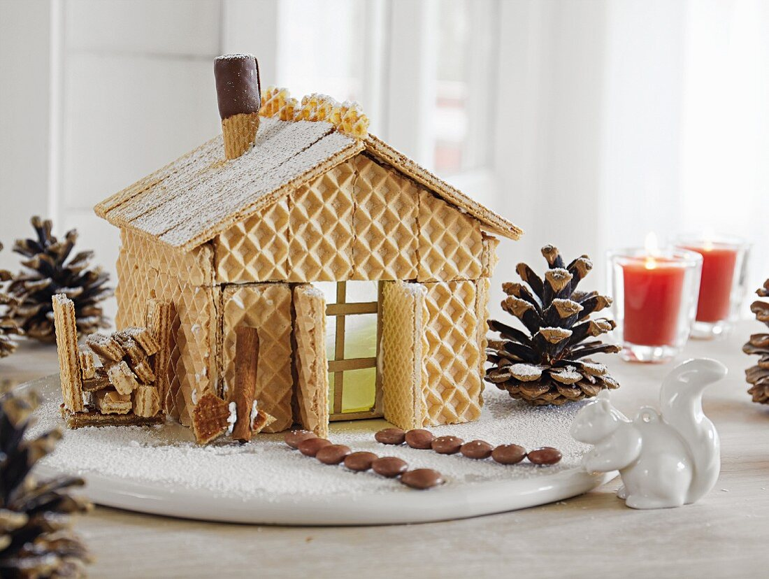 A small house made of waffles and decorated with chocolate sweets