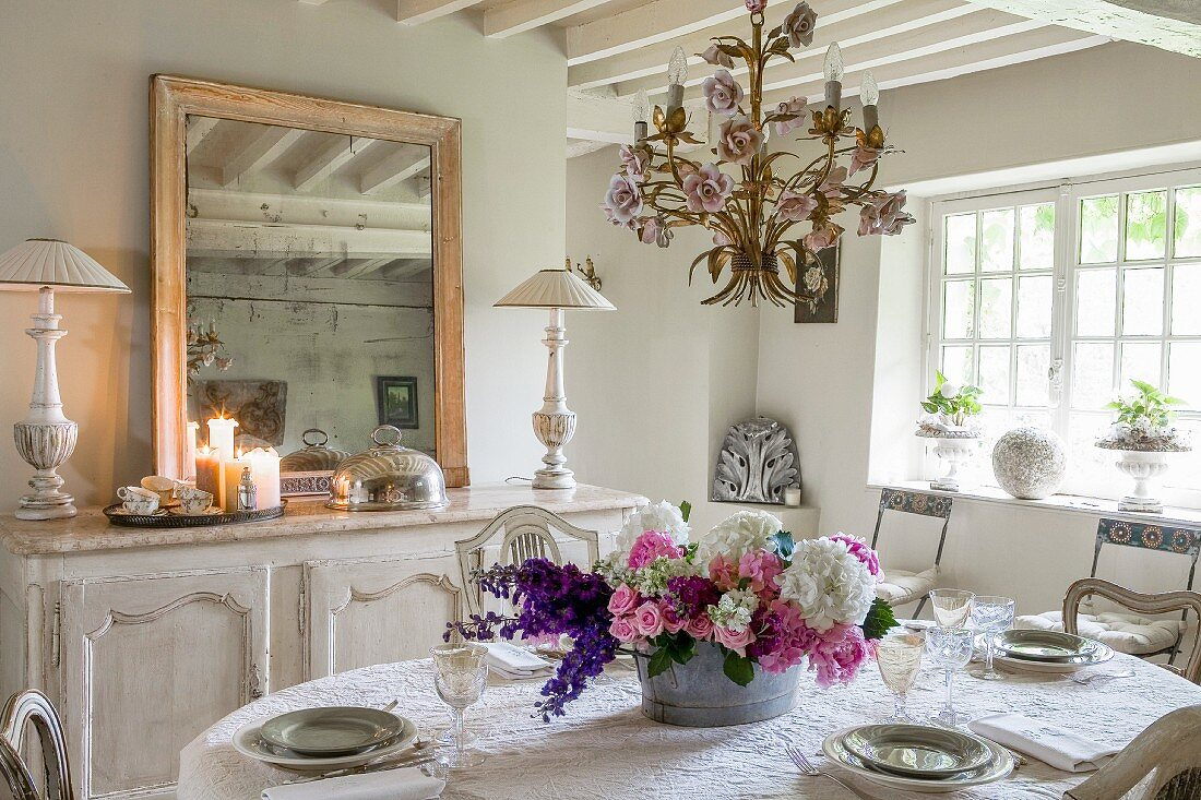 Arrangement of summer flowers on set table in dining room