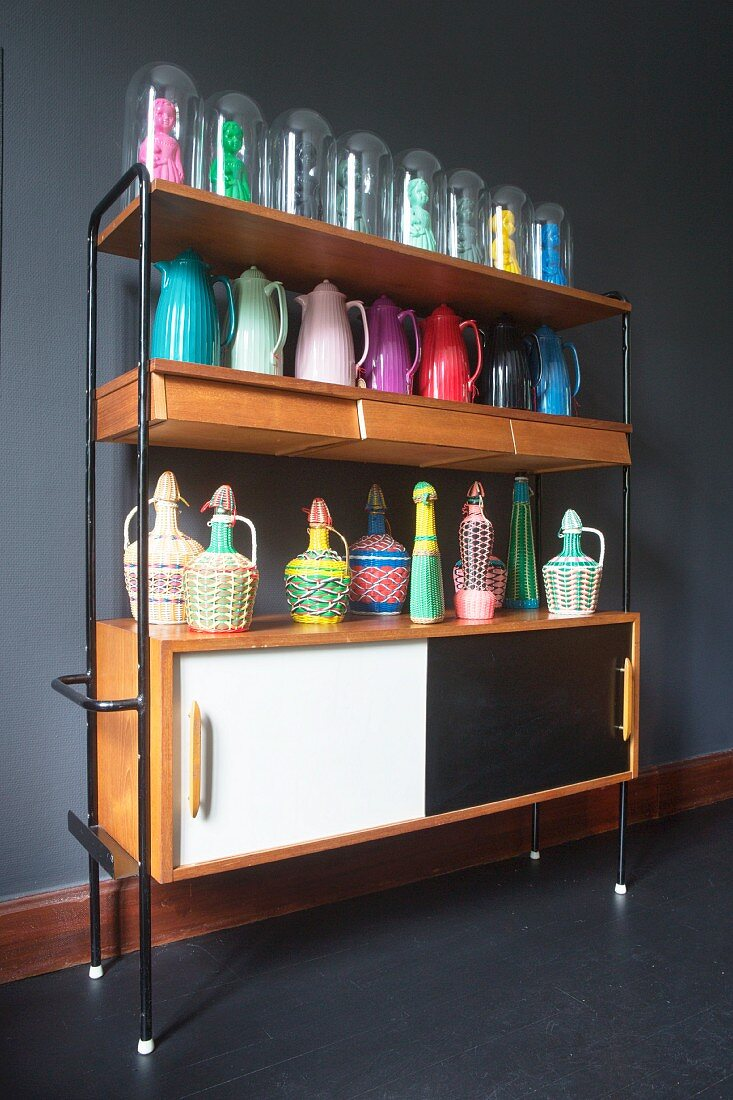 Various colourful thermos flasks, wicker bottle covers and figurines of women under glass covers on shelves above retro sideboard