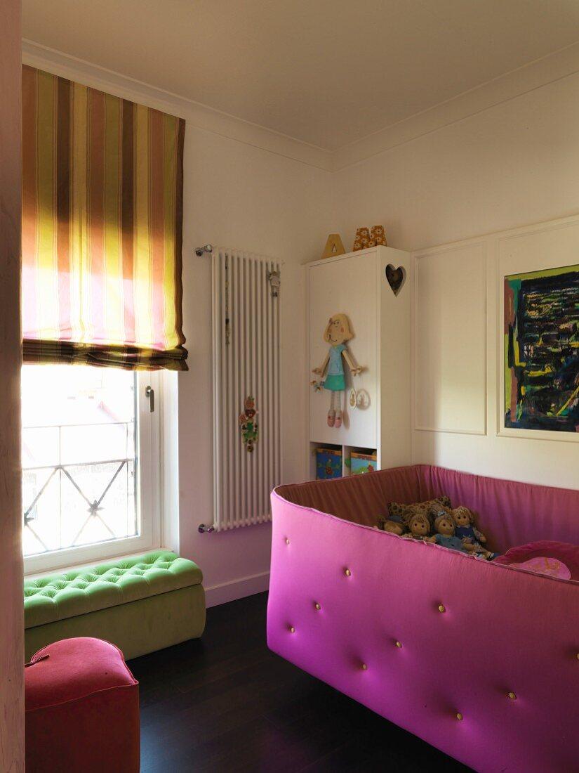 Mädchenzimmer mit pinkfarbenem, gepolstertem Kinderbett